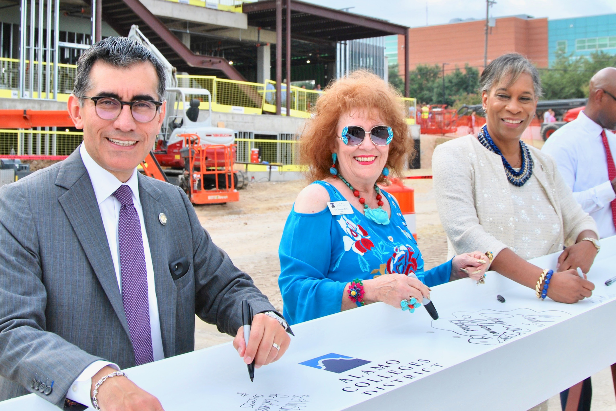 Chancellor Flores, Trustee Katz, and Dr. Loston signing a building beam outside